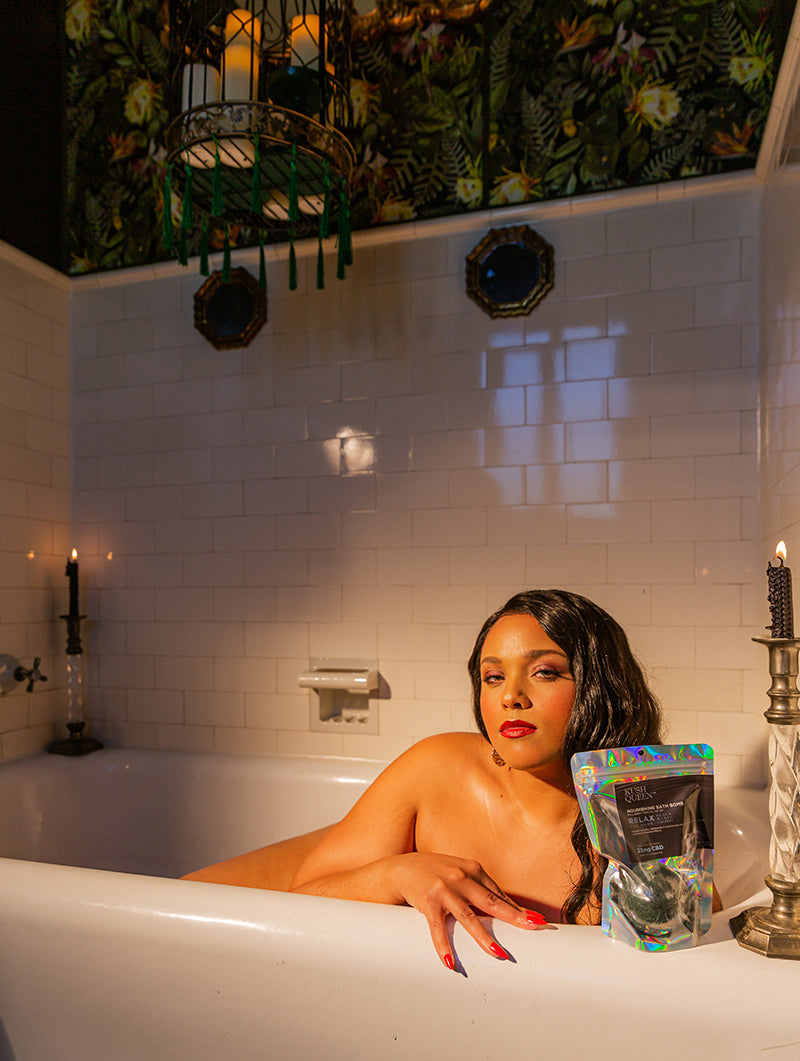 Model laying in a tub holding a 100mg Black Magic CBD Bath Bomb