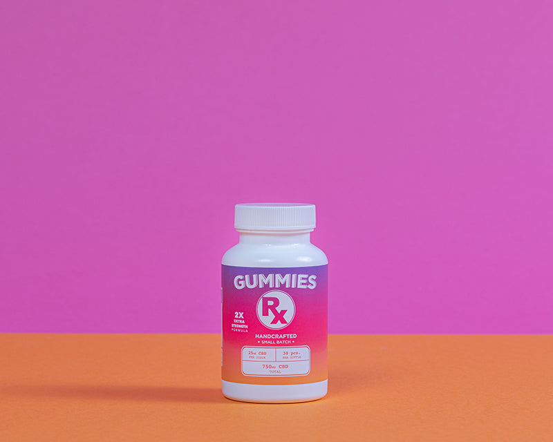 Kush Queen CBD Gummies Rx 750mg shown in it's bottle with a pink and orange background.