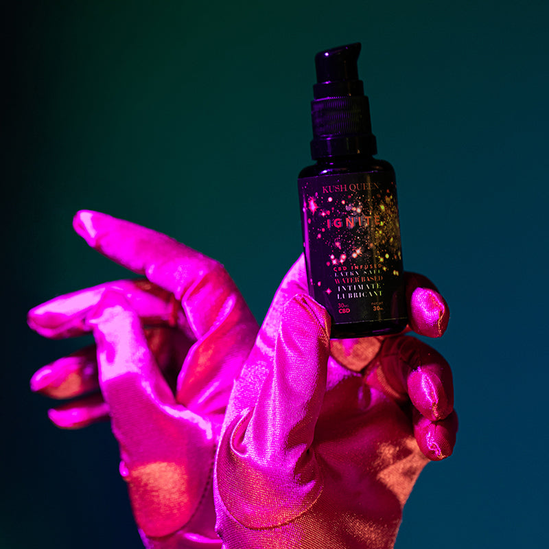 Red silk gloves holding a bottle of Kush Queen Personal Lube.