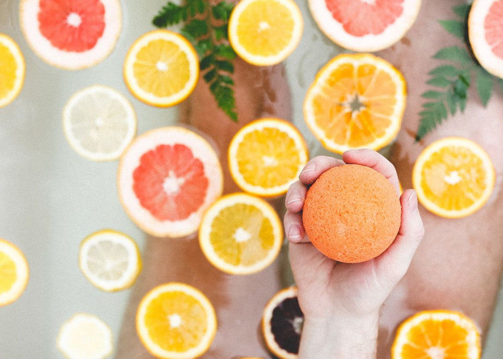Vitamin C and CBD are great ways to boost your immune system during COVID 19. Our Citrus bath bomb is shown over a tub of fresh cut citrus fruits.