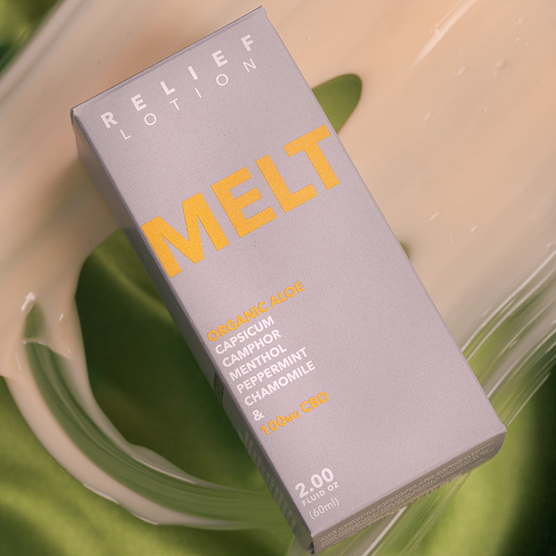 Kush Queen Melt CBD Relief Lotion shown in its packaging laying on a green silk.
