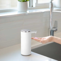 rechargeable liquid soap sensor pump - white finish - lifestyle with hand using pump in kitchen