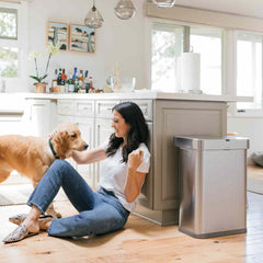 58L rectangular sensor bin with voice and motion control - brushed stainless steel - lifestyle woman and dog image