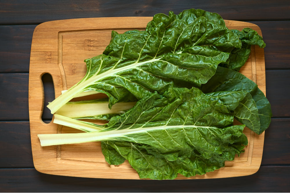 Chard on a cutting board - a great leafy green vegetable to add to your keto grocery list