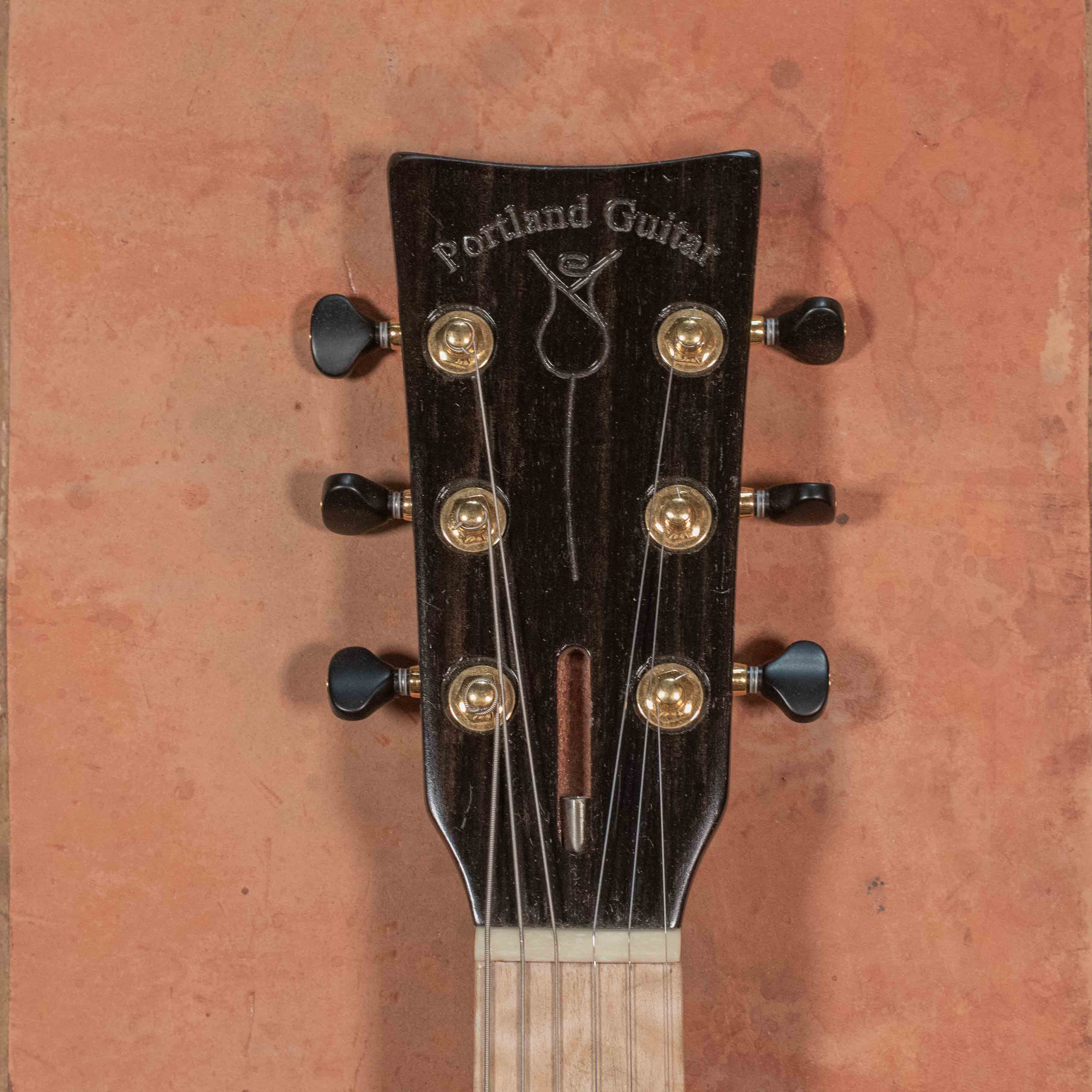 The logo of Portland Guitar. A rose on a guitar headstock with black tuners.