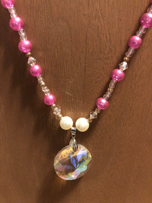 Beautiful Pink and clear beaded necklace with 2 white beads surrounding a glass prism pendants.