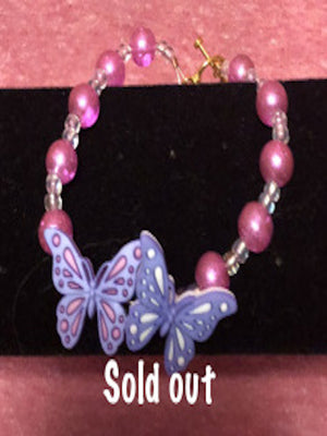 Beautiful faux pink pearl and clear seed beads with purple butterflies in the center