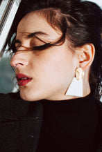 Load image into Gallery viewer, Close up of model'd face wearing black clothes with statement white and gold trapezoid earrings