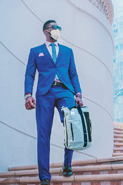 man in a suit wearing the kn95 n95 masks while holding the anvanda great freakin bag