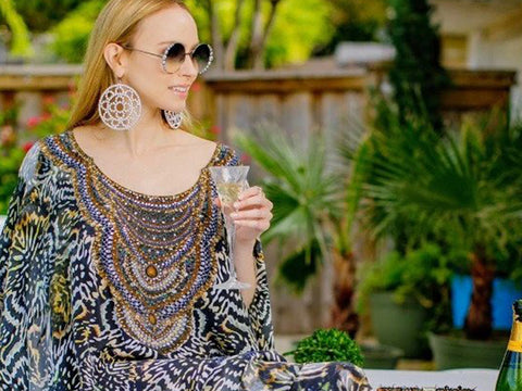 An image of a woman sitting on a table with a glass of champagne in her hand.