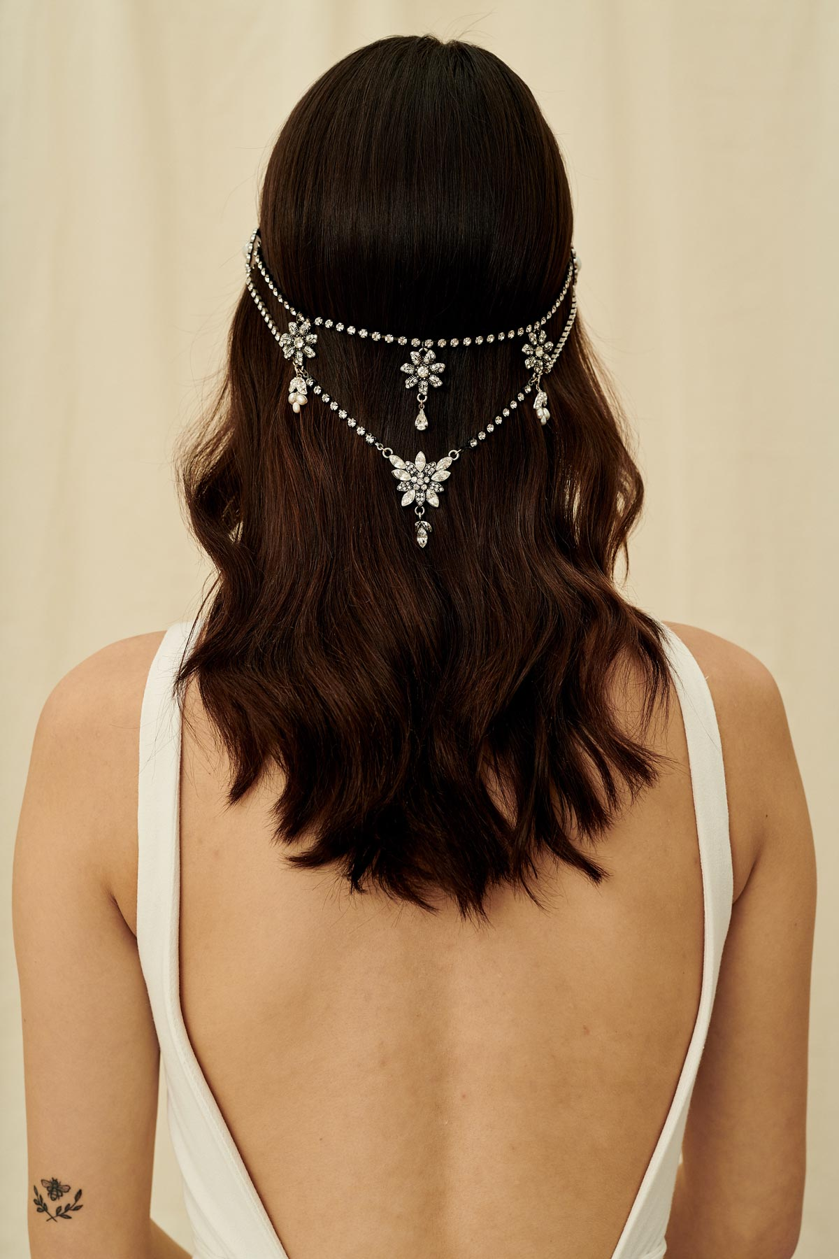 A Gatsby-inspired bridal hair accessory made with multiple strands of antique crystal chain and wired with freshwater pearls