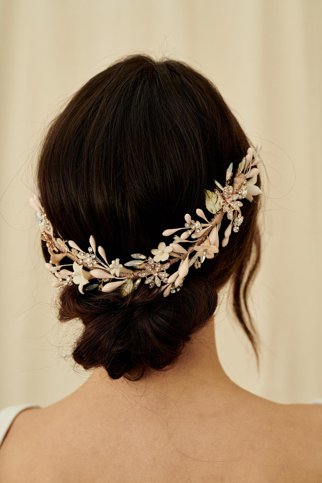 A statement bridal hair accessory featuring porcelain and wax flowers, crystals and opals, all wired onto a comb