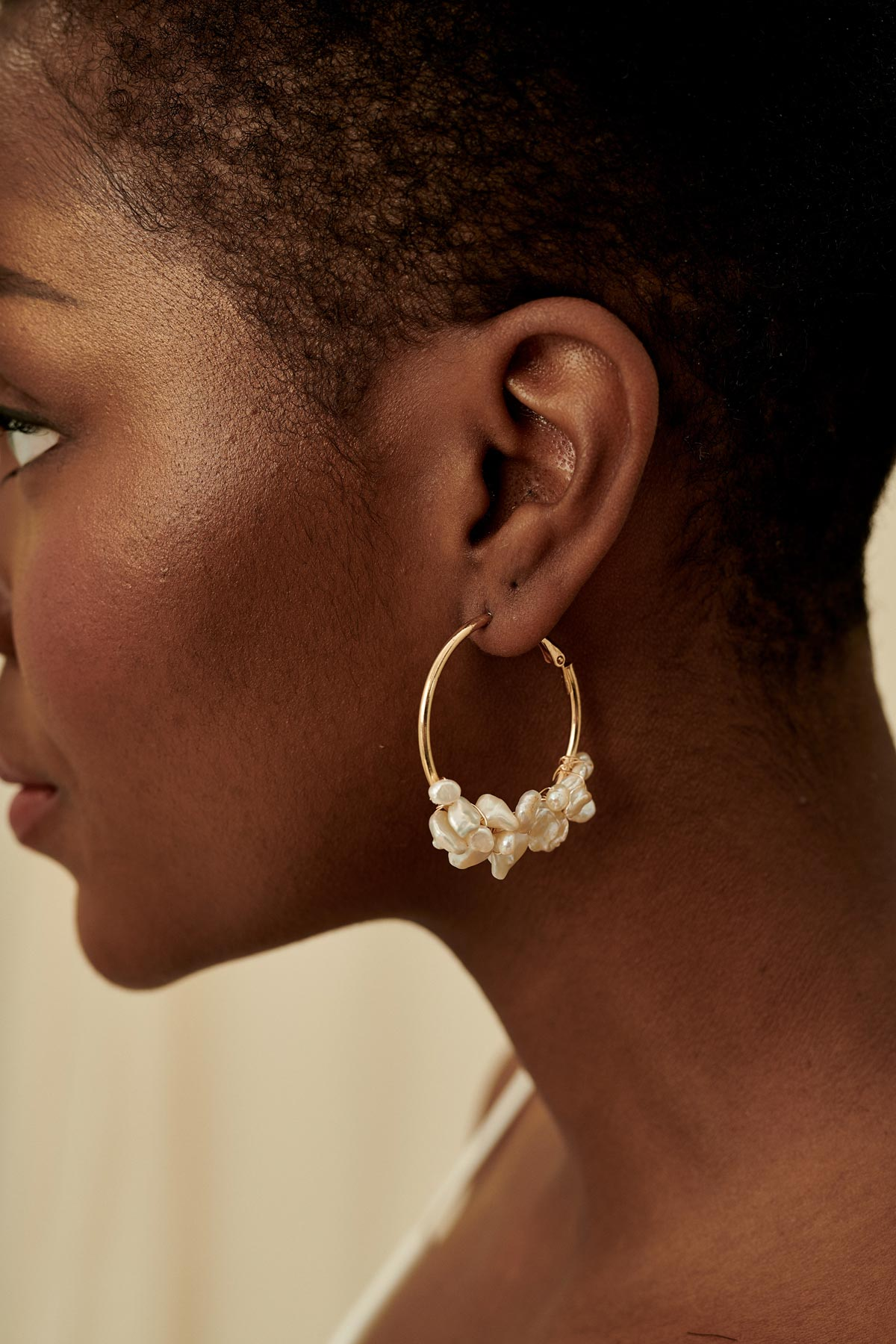 Intricate gold hoop earrings wired with freshwater pearl clusters.