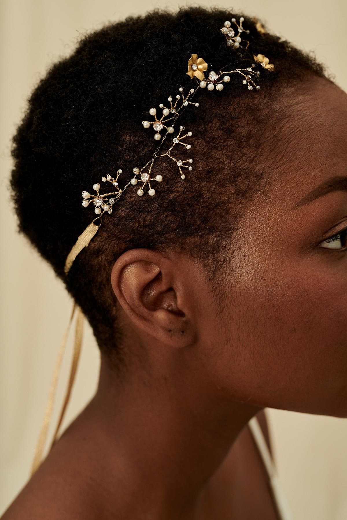 A gold wired bridal hair vine with brass flowers, glass beads, and glittery crystal clusters