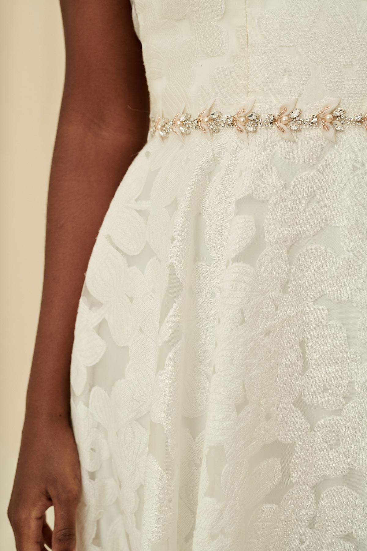 A delicate and feminine bridal belt made with crystals, pearls, glass beads, and soft fabric flower petals