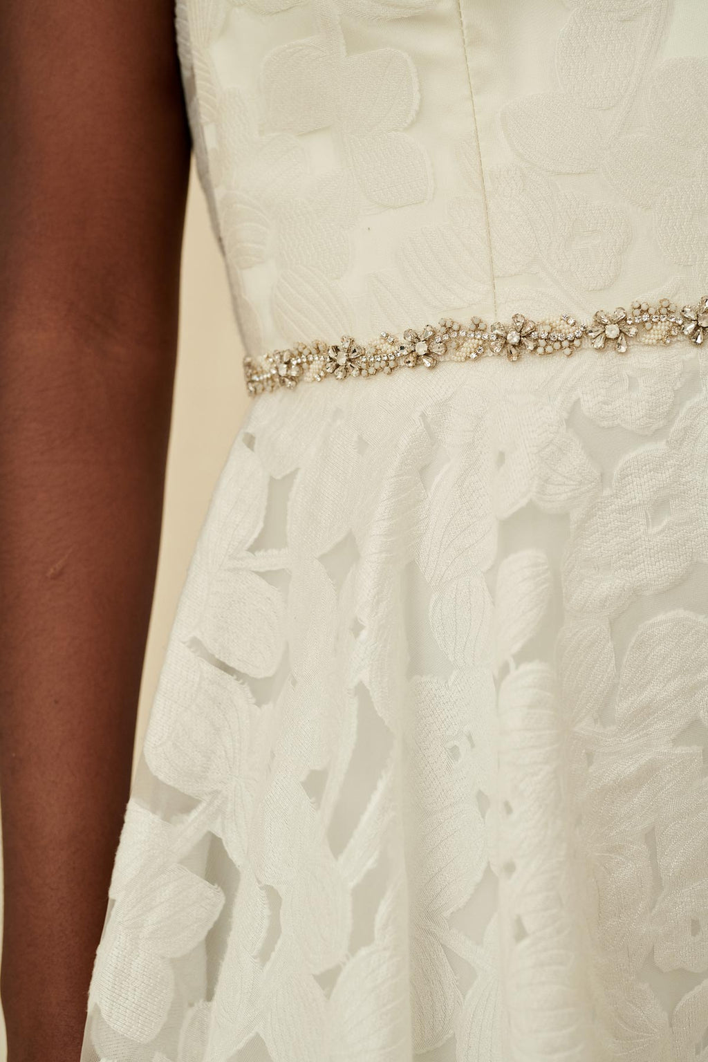 A delicate bridal belt with silver cased teardrop crystals, seed beads , and opaque glass beads in a swirling floral pattern