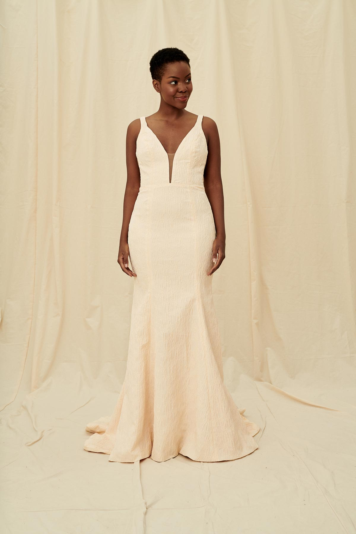 Coloured wedding gown in a crinkly blush fabric with a plunging front and back and a long train