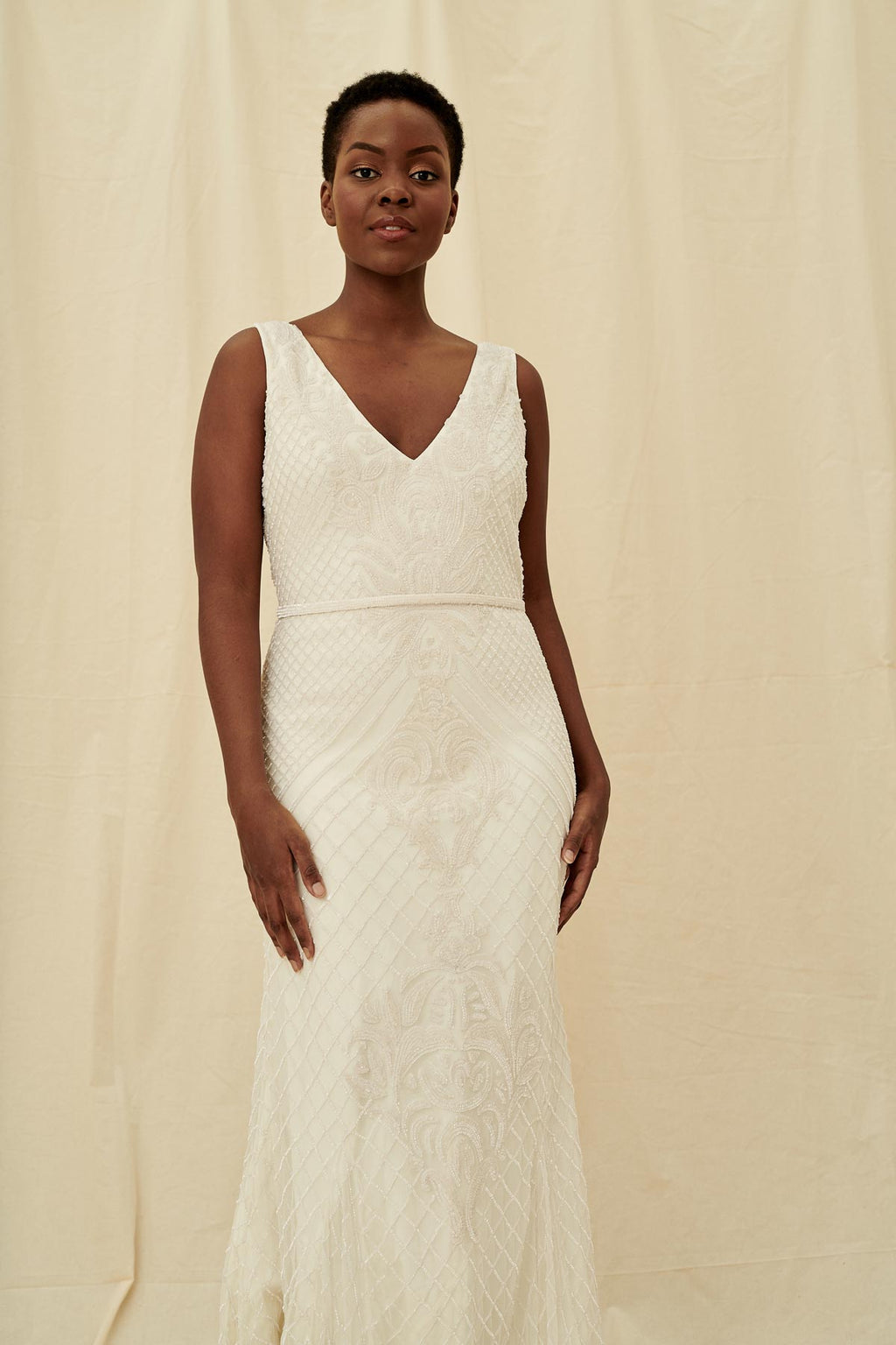 An elegant wedding dress with a simple beaded v neck bodice, scoop back, and fitted silhouette.