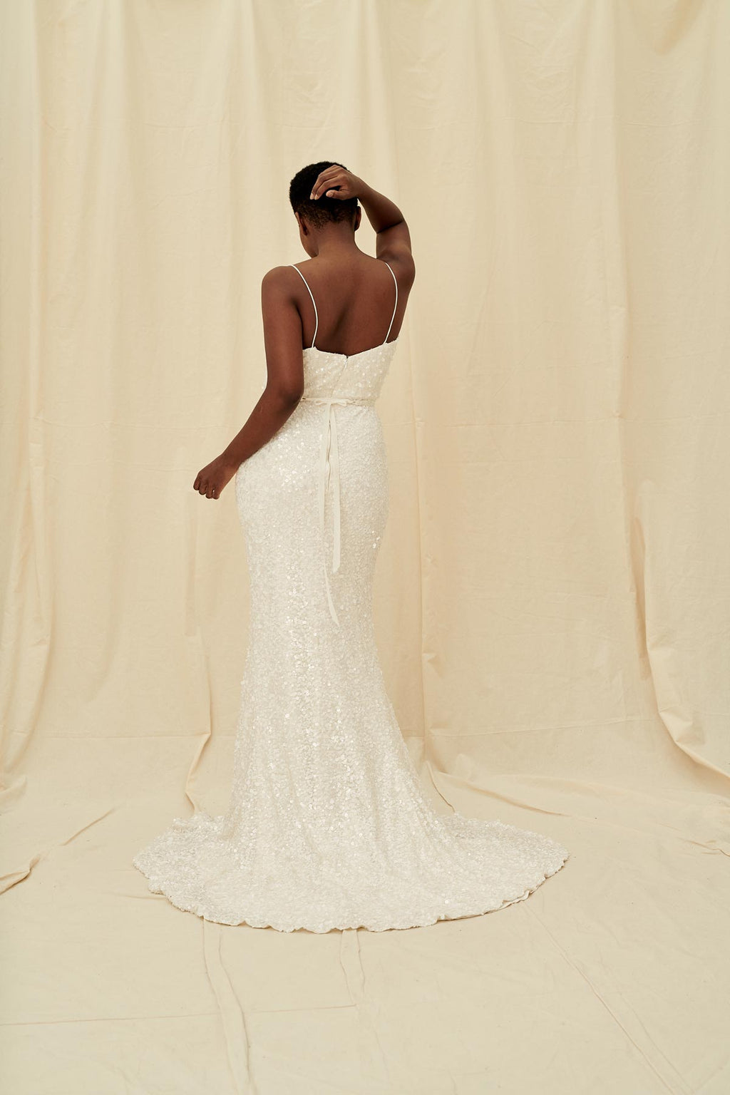 Pearly matte sequin wedding gown with spaghetti straps, a sheath skirt, and a train