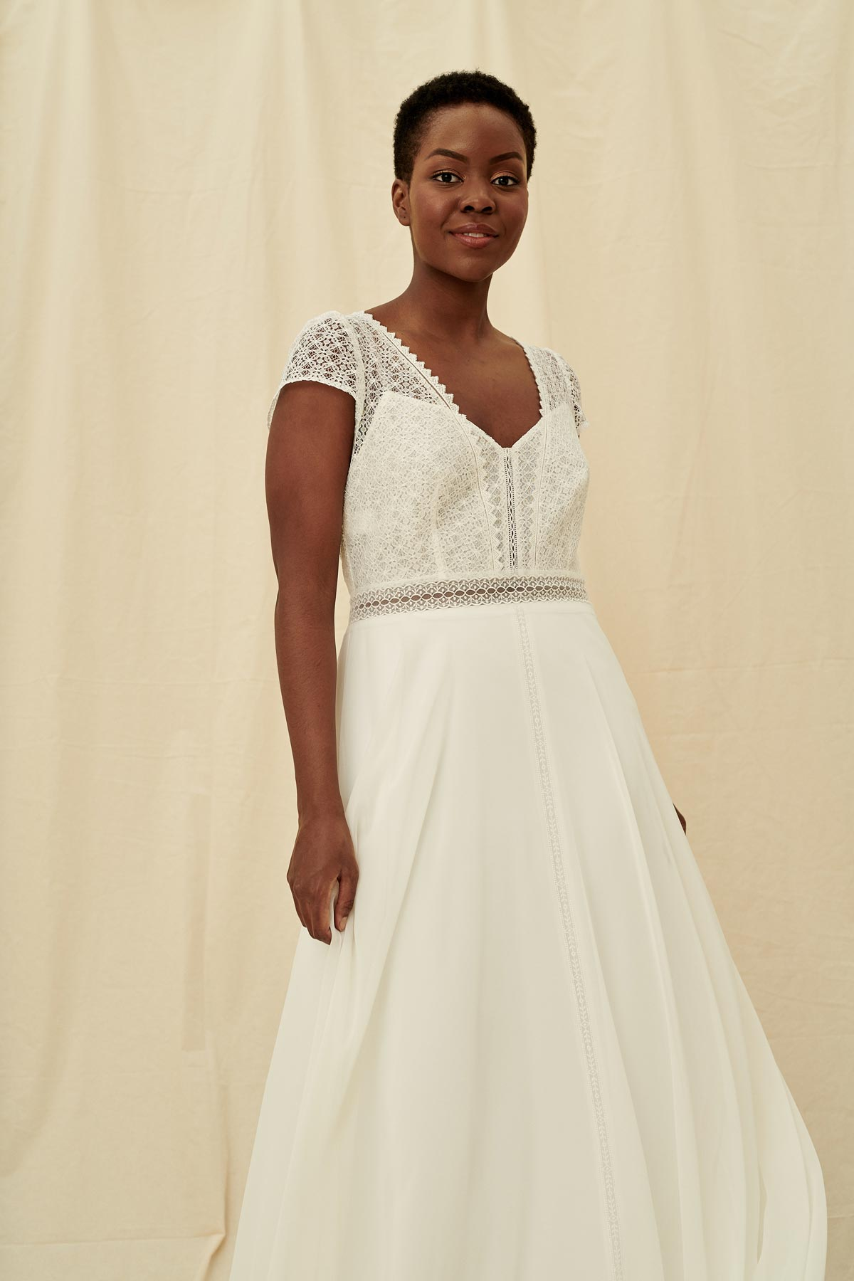 A unique wedding gown featuring a sweetheart bodice with a short sleeve t-shirt lace overlay, keyhole back, and lace waist panel.