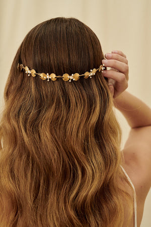 A delicate and feminine bridal hair accessory featuring a gold half-circle tiara set with textured petals and freshwater pearls