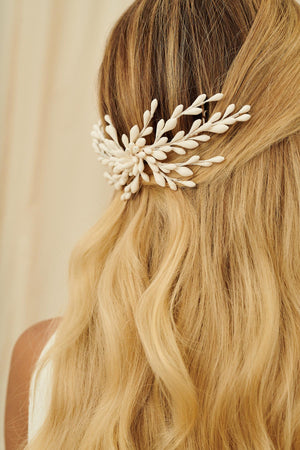 A delicate bridal hair accessory made from wax orange blossoms set into a comb