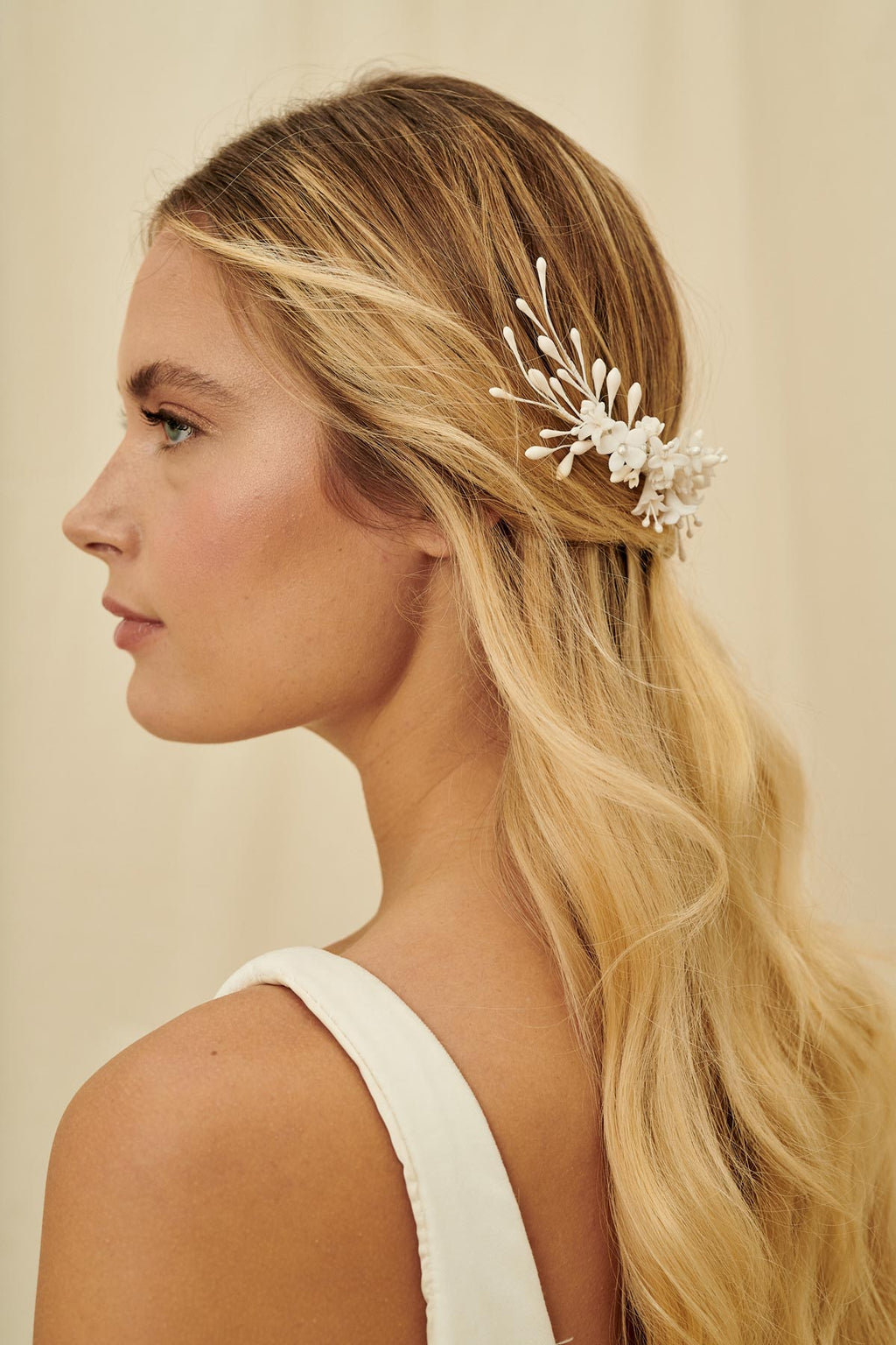 An asymmetrical bridal hair comb wired with wax orange blossoms and porcelain flowers