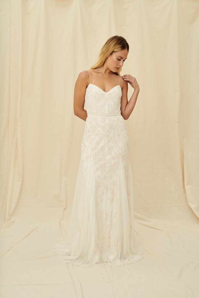 A fitted wedding gown with spaghetti straps and a sweetheart neckline, floral beading, embroidery, and a dramatic train