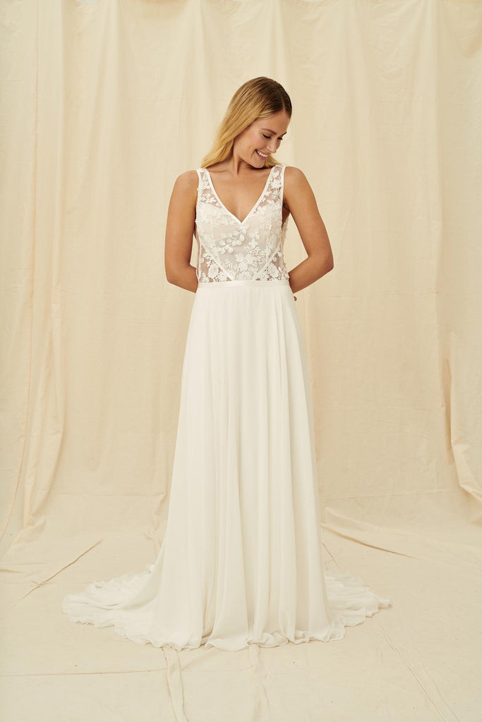 A modern wedding gown with a sheer lace bodice, plunging back and string tie, and a flowy skirt