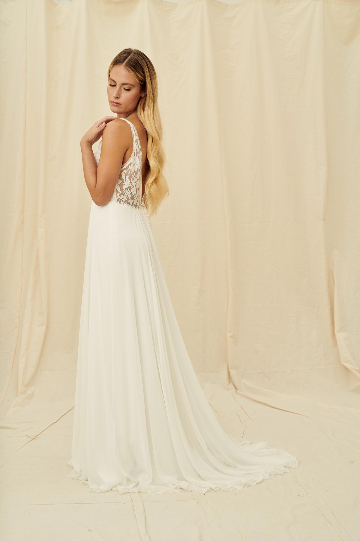 An elegant wedding gown with a deep v bodice and sheer lacy open back, gathered skirt and train