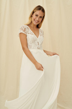A non-traditional wedding dress with a sheer floral bodice, short sleeves, lacy button-up back, and a fluttery skirt