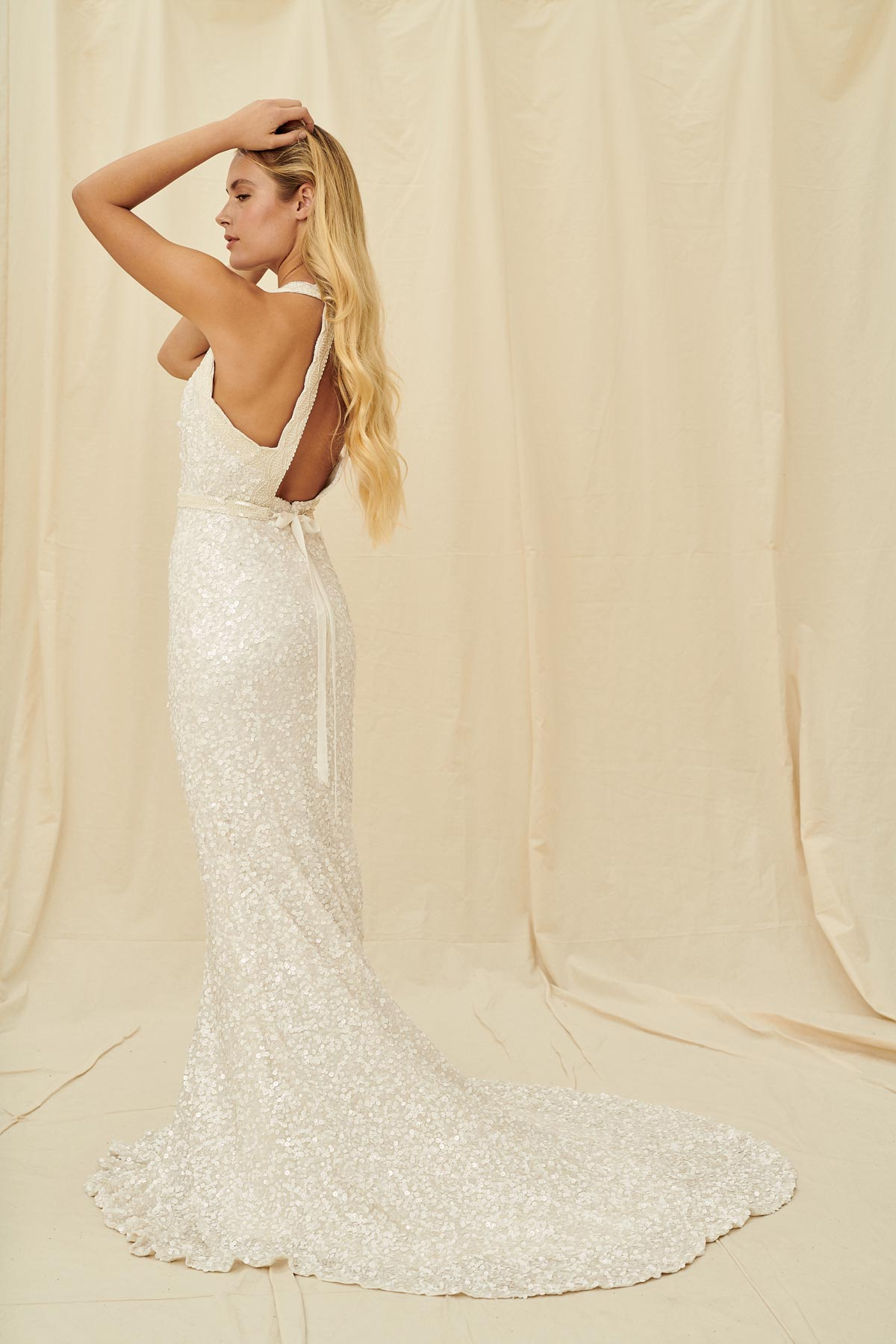 A unique beaded wedding dress with a high neck, keyhole back and a fitted skirt with in a train