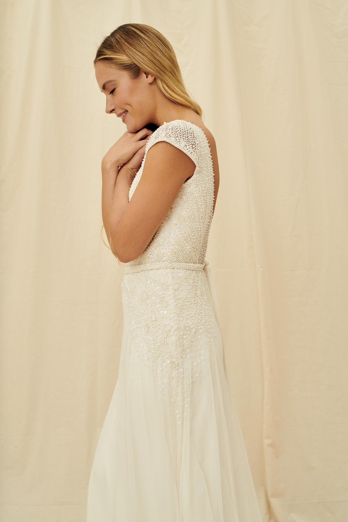 A romantic wedding dress with a tulle skirt, beaded cap sleeves, and a super low back