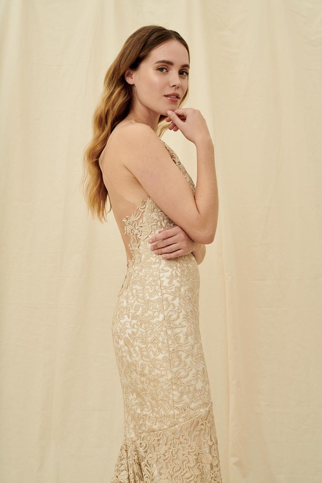 Shimmery golden wedding gown with a fitted skirt, train, and mesh illusion front and back for a backless look.