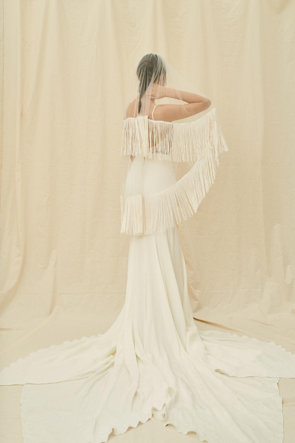 A fingertip length boho veil with a long fringe trim