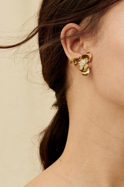 Modern and stylish clip-on bridal earring featuring raw quartz nestled within gold blooming flower petals.