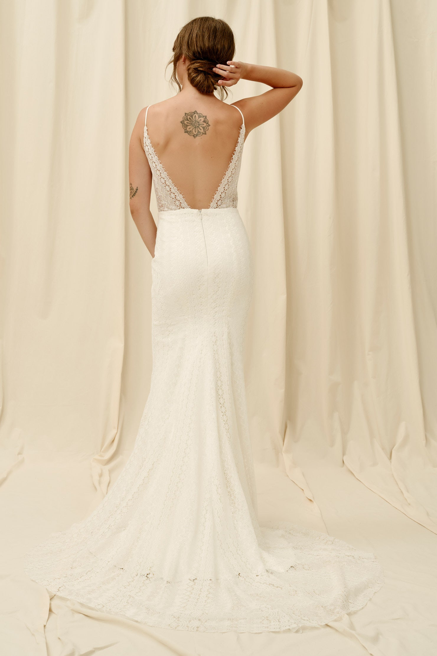 Fitted lace wedding dress with spaghetti straps and a long train