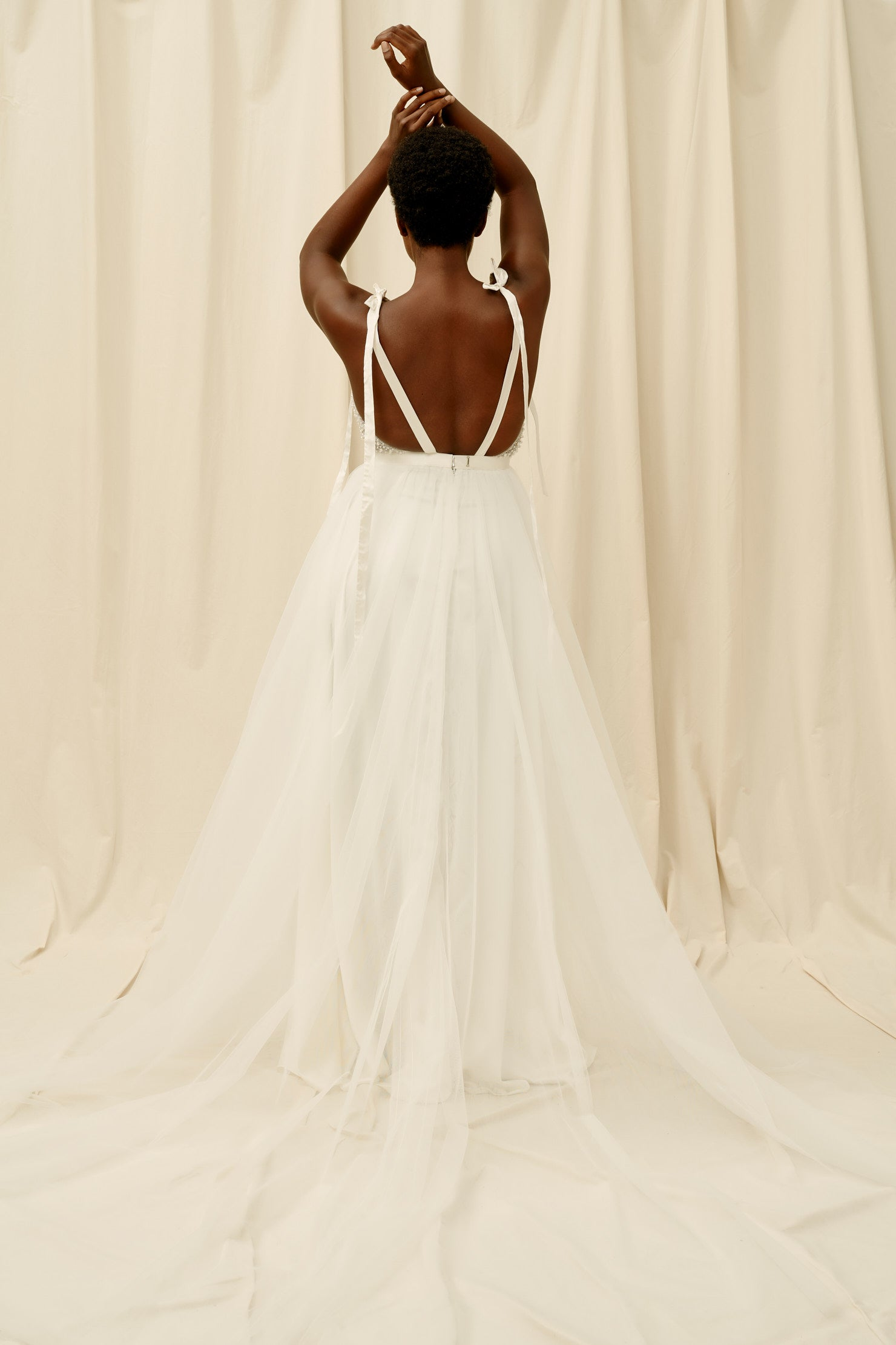 Open backed wedding dress with a soft tulle skirt and a long train
