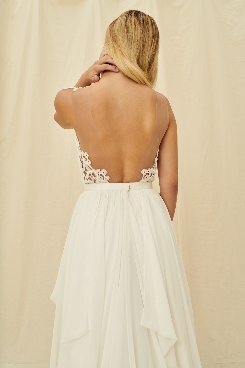 A backless dress with an illusion neckline, modern floral lace, and a pickup skirt