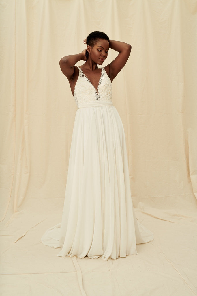 A flowy dress with a beaded bodice, open back, and a slit skirt by Truvelle