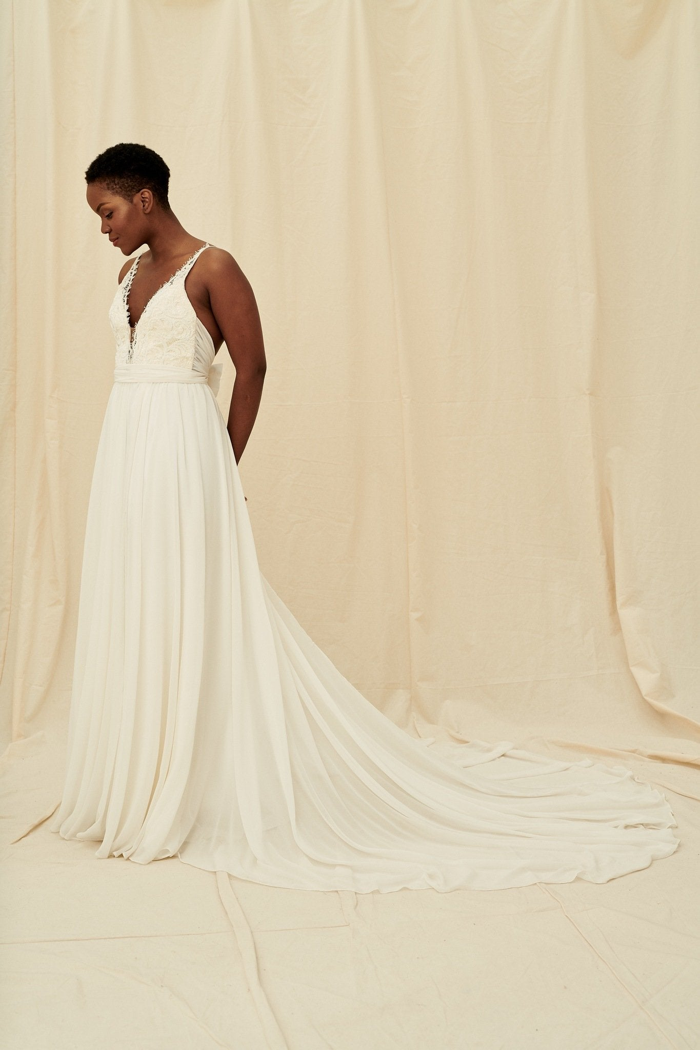 A romantic beaded wedding dress with wrap ties and a long train by Truvelle
