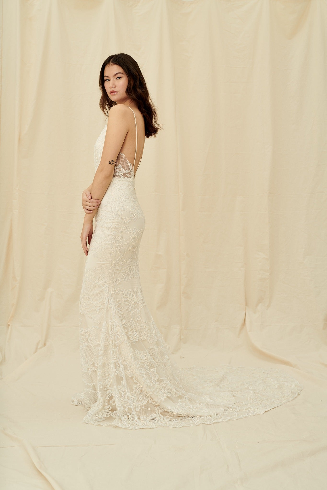 Fitted mermaid gown with a vintage-style beaded overlay and a long train