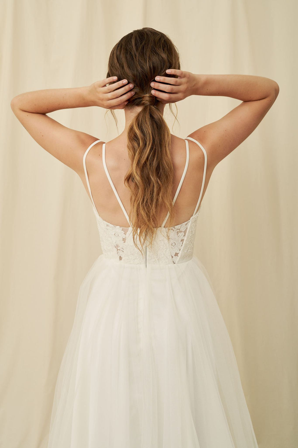 Delicate beaded wedding dress with double straps, geometrical cutouts, and a tulle skirt