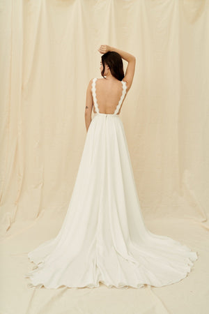All-crepe wedding gown with a long train, pockets, and delicate lace trim