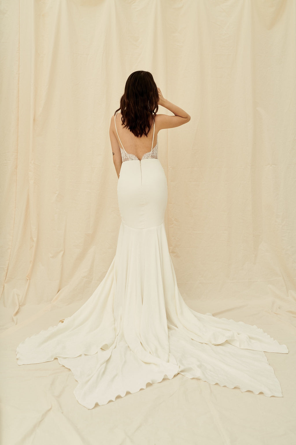 fitted crepe dress with lace sides, open back, and a unique long train