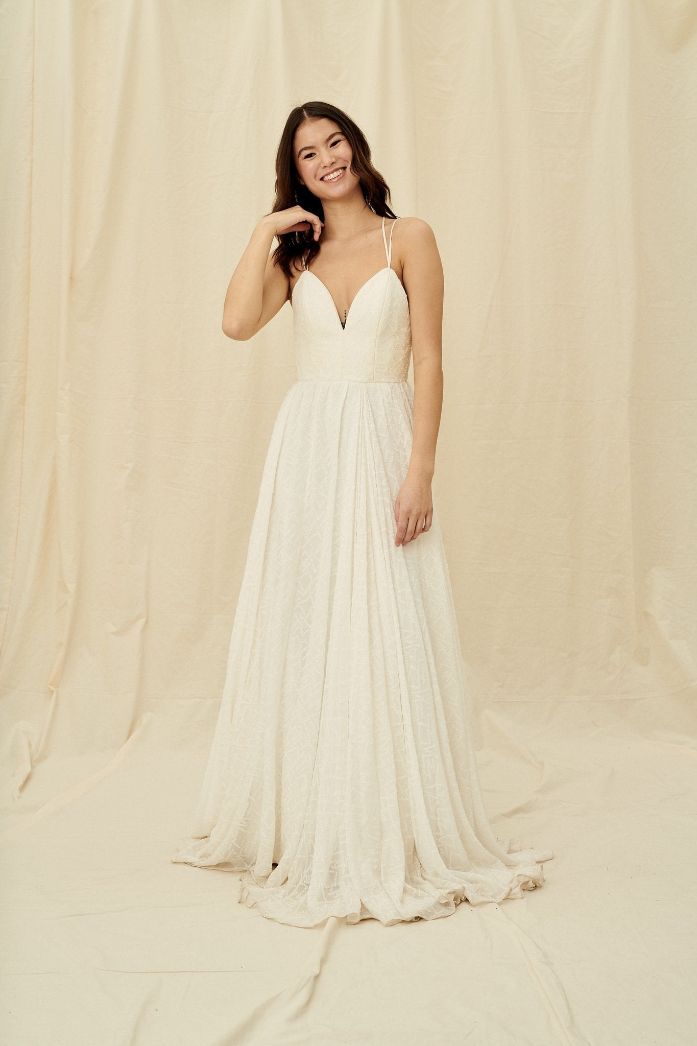 A textured chiffon gown with criss-cross back straps and a structured bodice by Truvelle
