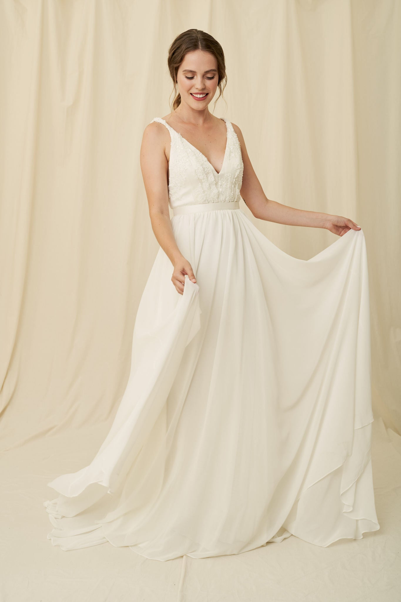 A lightweight wedding gown with a chiffon skirt and beaded lace lace on a plunging bodice with twisted straps.