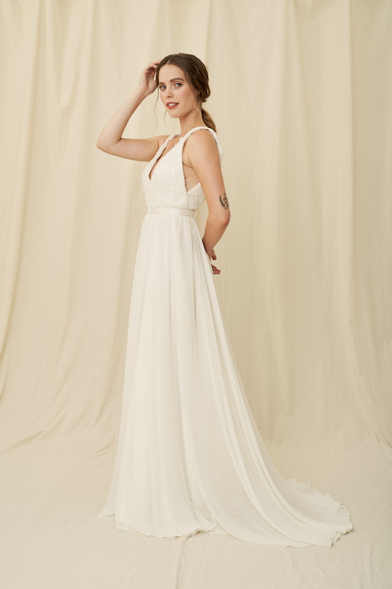 A lightweight wedding gown with a chiffon skirt and beaded lace lace on a plunging bodice with twisted straps by Truvelle