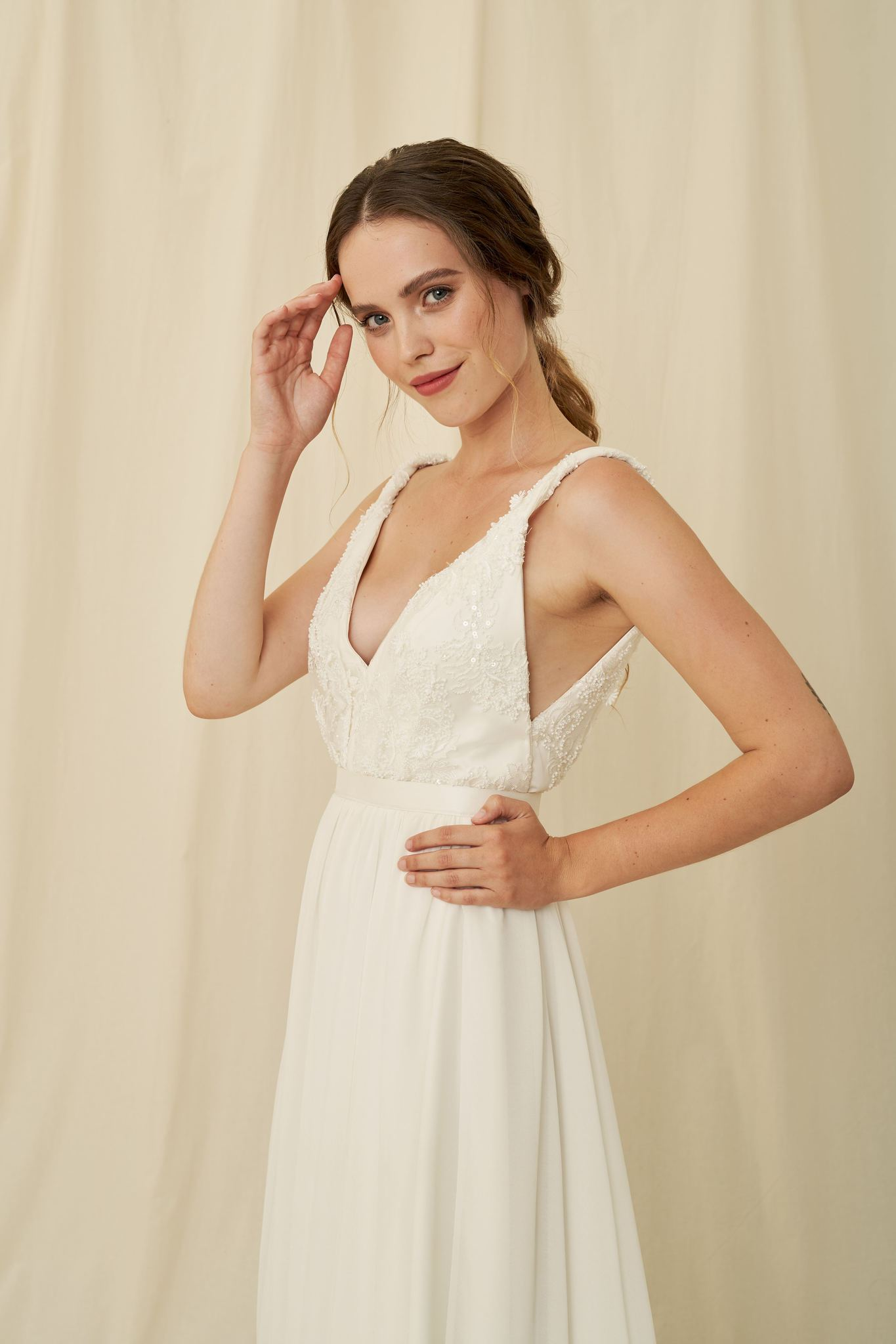 A lightweight wedding gown with a chiffon skirt and a bodice of beaded lace with twisted straps