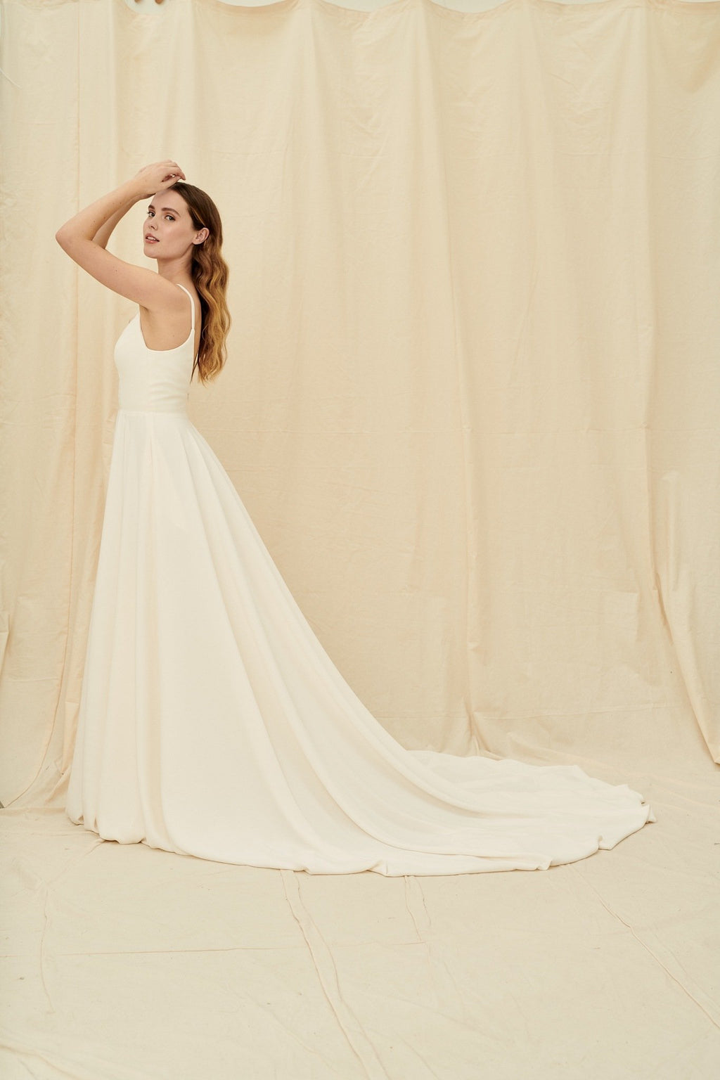 Super low cut crepe wedding dress with spaghetti straps, pockets, and a huge train
